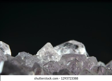 Quartz also called deep quartz with mineral inclusions in the studio in front of black background photographed in Marco mode