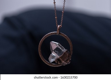 A quartz crystal necklace hangs from a pendant. Quartz is said to have metaphysical healing properties.