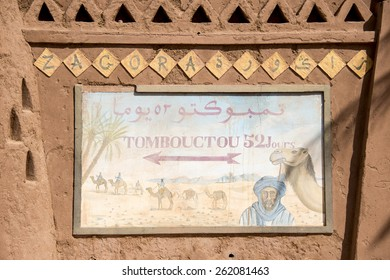 QUARZAZATE, MOROCCO, MARCH 8, 2014. A sign with a berber in the desert with a camel and an arrow pointing to Timbuktu, saying â??52 days to Timbuktuâ?� in Quarzazate, Morocco, on March 8th, 2014.