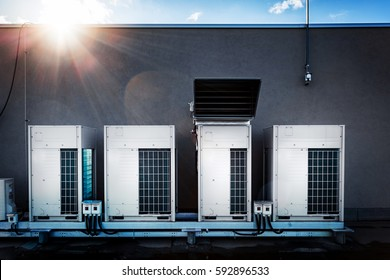Quaternary of air conditioning units in a row of juxtaposed on the gray wall of the roof. At the top of the image sunshine in the form of star flare and blue sky.