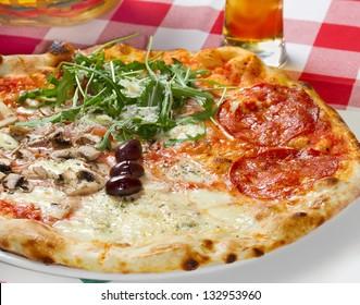 Quattro Stagioni (four seasons) pizza on a restaurant table. Studio shot
