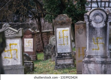 QUATZENHEIM, FRANCE - FEB 20, 2019: Front view of vandalised graves with nazi symbols in yellow spray-painted on the damaged graves - Jewish cemetery in Quatzenheim near Strasbourg