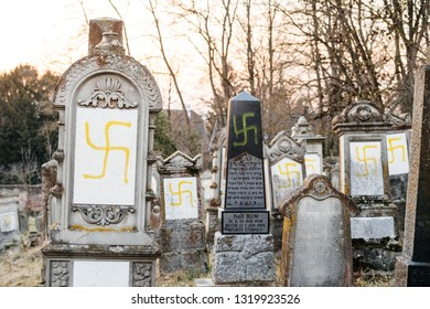 QUATZENHEIM, FRANCE - FEB 20, 2019: Vandalised graves with swastika nazi symbols in yellow spray-painted on the damaged graves - Jewish cemetery in Quatzenheim near Strasbourg