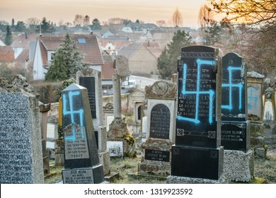 QUATZENHEIM, FRANCE - FEB 20, 2019: Sunset over Jewish cemetery in Quatzenheim near Strasbourg with vandalised graves in with nazi symbols in blue spray-painted on the damaged graves