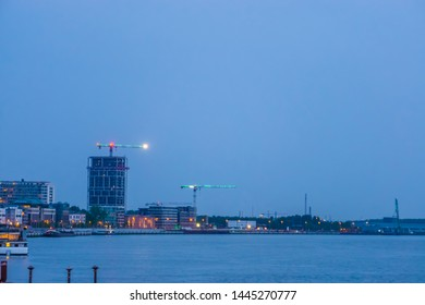 The quay of antwerp city with water and view on the lighted city by night, Antwerpen, Belgium