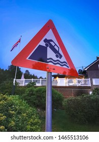 Quay side or riverbank road sign with Norwegian house and Norway flag background behind. Road signs in Norway. What to know in Norway.