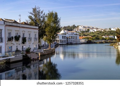 The quayside along the River Gilão in Tavira,Portugal with a view of the city in the background.