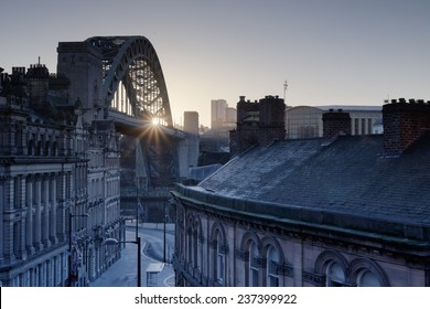 The Quayside at Newcastle upon Tyne and Gateshead photographed as the sun rises behind the Tyne bridge during the morning.