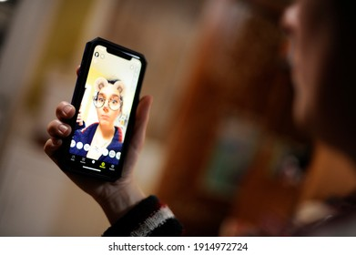 Quebec, Canada - 02-11-2021: Woman has fun with mouse face app with Snapchat
