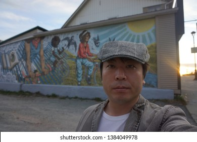 quebec, canada, 10 22 2017 : a man standing in front of mural painting at rue king ouest of sherbrooke town on the townships trail of eastern townships in quebec