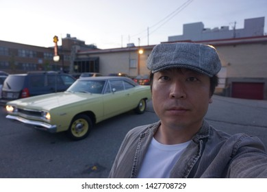quebec, canada, 10 22 2017 : a man standing in front of classic car named plymouth satellite parked at rue camirand of sherbrooke town on the townships trail of eastern townships in quebec