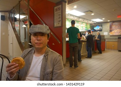 quebec, canada, 10 22 2017 : a man eating hamburger at fast food restaurant named louis at rue king ouest of sherbrooke town on the townships trail of eastern townships in quebec