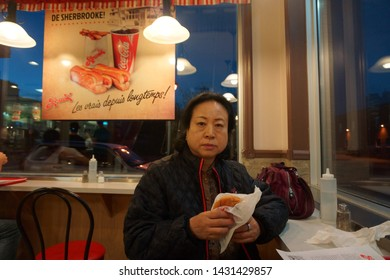 quebec, canada, 10 22 2017 : a woman eating hamburger at fast food restaurant named louis at rue king ouest of sherbrooke town on the townships trail of eastern townships in quebec