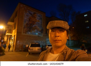 quebec, canada, 10 22 2017 : a man standing in front of mural painting at rue wellington south of sherbrooke town on the townships trail of eastern townships in quebec