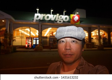 quebec, canada, 10 22 2017 : a man standing in front of provigo grocery store at rue queen of sherbrooke town on the townships trail of eastern townships in quebec in the night