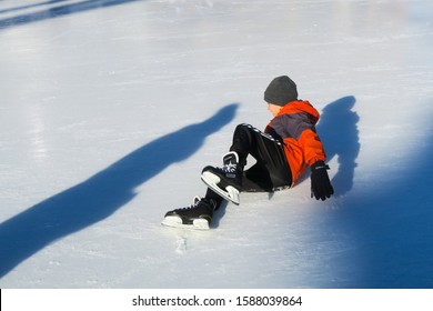 Quebec, Canada - december 2019 : young boy falling down on the ice during ice skating
