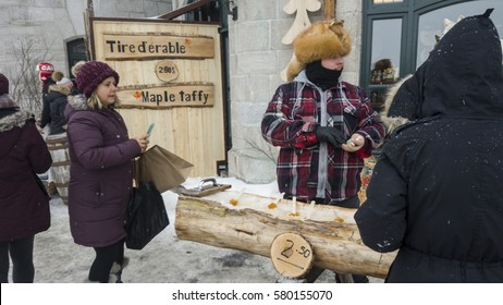 Quebec, Canada - December 28 2016: Maple taffy sugar candy with a wooden popsicle stick on snow in Quebec, Canada. A street vendor selling maple toffee made of hot maple syrup poured on snow.