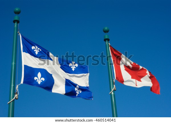 Quebec and Canada flags fluttering in the wind together on blue sky