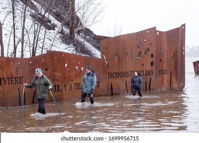 Quebec City, Quebec, Canada, April 10, 2020 - Three people wading out of water after a St. Lawrence River flash flood in the Cap-Rouge sector