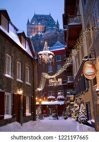 Quebec City, Canada - December 13, 2017: Rue du Petit-Champlain at Lower Town Architecture and View of Frontenac Castle at Night with Christmas Decorations and Lights and Snow on the Ground