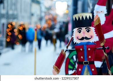 QUEBEC CITY - CANADA December 30, 2014.  Nutcracker figure on a street with snow and people walking in the background, stores with christmas lights displays prepare to receive the new year