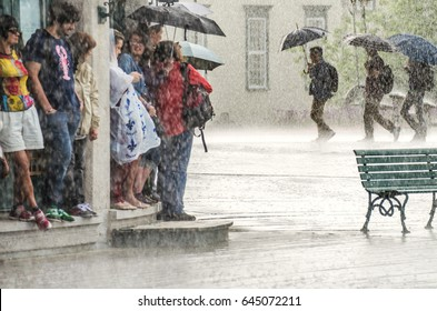 Quebec City, Canada - July 27, 2014: A group of people hide from heavy rain under a building while three walk with umbrellas