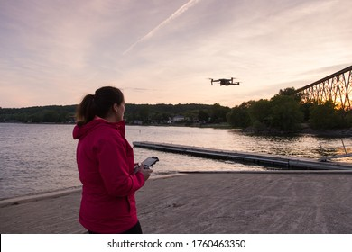 Quebec City, Quebec, Canada, June 20, 2020- Brunette young woman seen in profile flying a drone over a jetty in the Cap-Rouge sector