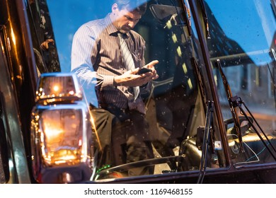 QUEBEC CITY, CANADA - MAY 21, 2018: Bus driver using his smartphone in Montreal.