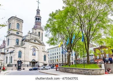 Quebec City, Canada - May 29, 2017: Old town street with flags and garden park called Place de l'Hotel-de-Ville and Notre Dame Cathedral