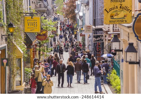 QUEBEC CITY, QUEBEC, CANADA - MAY 29, 2004:  Tourism on Petit Champlain Street, in Old Quebec City. People walk along the narrow street shopping for souvenirs.