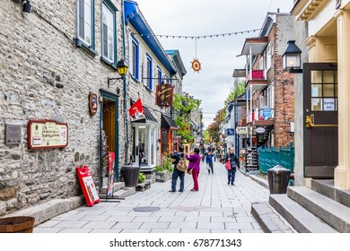 Quebec City, Canada - May 30, 2017: Lower old town street Rue du Petit Champlain with people tourists walking, cobblestone road and hanging decorations by restaurant