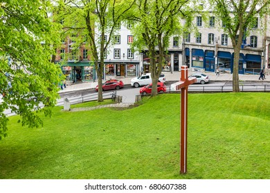 Quebec City, Canada - May 30, 2017: Montmorency Park National Historic Site with red cross in green grass field and stone wall by old town street called Cote de la Montagne