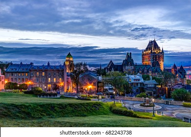Quebec City, Canada - May 30, 2017: Cityscape or skyline of Chateau Frontenac, park and old town streets during sunset with illuminated castle and Saint Denis street buildings