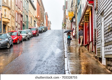 Quebec City, Canada - May 31, 2017: Old town steep street during heavy rain with drops and wet road by restaurants and people walking with umbrellas