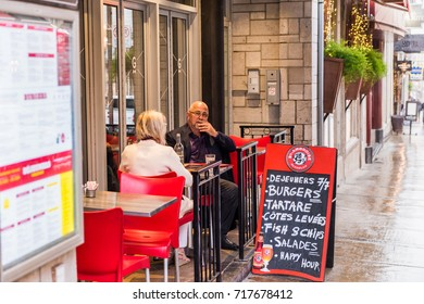 Quebec City, Canada - May 31, 2017: Old town street Saint-Jean during heavy rain with drops and wet road by restaurant and people or senior couple eating