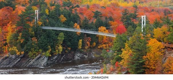 Quebec city, Quebec Canada - October 15, 2018 : Chaudière River Suspension Bridge at Chaudière Falls Park surrounded with fall foliage.