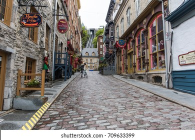 QUEBEC CITY, CANADA - SEPT 5, 2017: View of back alley behind the castle hotel at the foot of the hill, showing an unidentifiable tourist mounting on a bike.