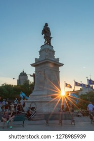 Quebec City, QC/CAN - 07-18-2017:  Tourists sitting on benches around the historic Samuel de Champlain monument in Old Quebec as the sun goes down