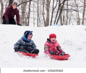 QUEBEC CITY QC/CANADA DECEMBER 03 2017 Brother and sisters (5 and 3 yrs old) sledging together in Quebec in winter, while mum looks on