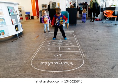 QUEBEC CITY QC/CANADA DECEMBER 17 2017  Playing hopscotch on an indoor hopscotch game in a public library in Quebec Canada