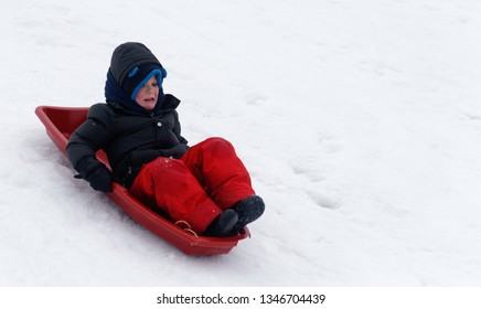 QUEBEC CITY QC/CANADA MARCH 06 2018  A little boy (5 yr old) looking scared as he sledges down a steep icy slope while sledging in Quebec City