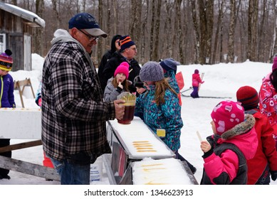 QUEBEC CITY QC/CANADA MARCH 14 2018 Children eating maple syrup taffy poured on ice at a sugar shack in Quebec, Canada