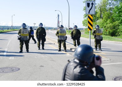 QUEBEC CITY-JUNE 8:  A press photographer taking pictures of the riot police during a rally to protest the G7 summit  on June 8 2018 in  Quebec City