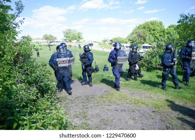 QUEBEC CITY-JUNE 8: Riot police officers pushing back protesters from a hill during a rally to protest the G7 summit  on June 8 2018 in  Quebec City