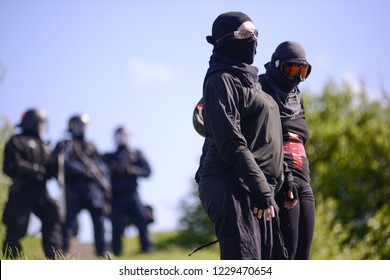 QUEBEC CITY-JUNE 8: Two protesters standing in front of the riot police officers on top of a hill during a rally to protest the G7 summit  on June 8 2018 in  Quebec City