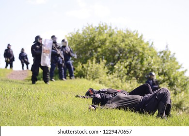 QUEBEC CITY-JUNE 8: Two protesters lying down in front of the riot police officers on top of a hill during a rally to protest the G7 summit  on June 8 2018 in  Quebec City