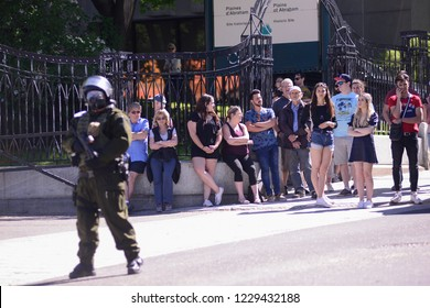 QUEBEC CITY-JUNE 9: Citizens and tourists standing on the sidewalk while police is protecting the streets during a rally to protest the G7 summit  on June 9  2018 in  Quebec City ,Canada