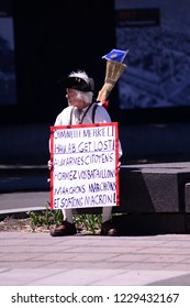 QUEBEC CITY-JUNE 9: A lonely aged protester sitting with a sign denouncing Angela Merkel during a rally to protest the G7 summit  on June 9  2018 in  Quebec City ,Canada