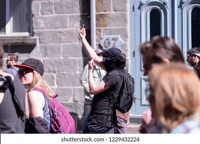 QUEBEC CITY-JUNE 9: A protester showing his middle finger towards the police during a rally to protest the G7 summit  on June 9  2018 in  Quebec City ,Canada