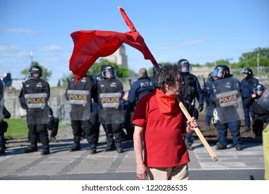 QUEBEC CITY-JUNE 9:  A protester standing in front of the riot police during a rally to protest the G7 summit  on June 9  2018 in  Quebec City ,Canada